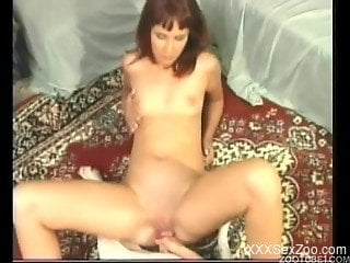 Redhead chick with small tits fucks with a cute white dog