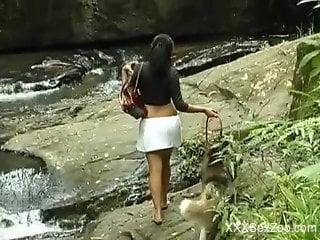 Stunning brunette fucks a dog by a waterfall